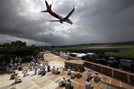 An aircraft prepares to land as Muslims gather to offer prayers on the rooftop of a mosque during Ramadan in Mumbai September 3, 2010. REUTERS/Danish Siddiqui/Files