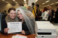 Washington hizo historia el jueves al convertirse en el primer estado de Estados Unidos en legalizar la posesión de marihuana para uso recreativo en los adultos, el mismo día en el que también entró en vigor la otra ley que legaliza el matrimonio entre personas del mismo sexo. En la imagen, Jeri Andrews (a la izquierda), de 43 años, y Amy Andrews, de 33, sostienen su licencia de matrimono en Seattle, Washington, el 6 de diciembre de 2012. REUTERS/Marcus Donner