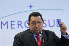 El presidente venezolano, Hugo Chávez, no asistirá a la cumbre de la unión aduanera Mercosur que tendrá lugar el viernes en Brasilia, dijeron fuentes oficiales, en medio de especulaciones sobre su salud mientras se somete a un tratamiento complementario para el cáncer. Imagen de archivo de Chávez con una copia de la constitución venezolana en una rueda de prensa tras reunirse con los presidentes de Mercosur celebrada el pasado mes de julio en el Palacio de Planalto, en Brasilia. REUTERS/Ueslei Marcelino