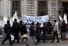 """El partido de Silvio Berlusconi retiró el jueves su apoyo al primer ministro italiano, Mario Monti, originando un conflicto que podría forzar la celebración de elecciones anticipadas. En la imagen del 6 de diciembre, unos ciudadanos pasan ante una pancarta que dice """"Silvio, Italia cree en ti"""", colgada fuera de su casa en el centro de Roma. REUTERS/Alessandro Bianchi"""