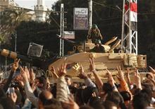 La Guardia Republicana de Egipto restauró el orden alrededor del palacio presidencial el jueves tras los fuertes enfrentamientos ocurridos durante la madrugada, aunque las hostilidades, que han causado siete muertos en las últimas semanas, se mantenían por los profundos desacuerdos sobre el camino que debe tomar el país. En la imagen del 6 de diciembre, varios manifestantes cantan lemas contra el presidente Mursi ante una barricada vigilada por un tanque fuera del palacio presidencial de El Cairo. REUTERS/Asmaa Waguih