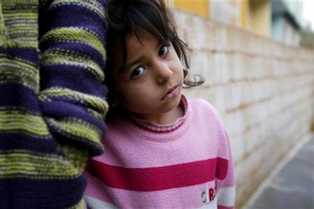 A Syrian refugee girl stands with her mother outside their friend's house at the Syrian-Turkish border town of Ceylanpinar, Sanliurfa province, December 6, 2012. REUTERS/Laszlo Balogh