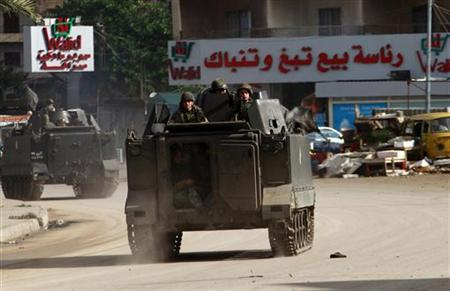 Lebanese Army soldier patrol on their military vehicles in the Sunni Muslim Bab al-Tebbaneh neighbourhood, in Tripoli, northern Lebanon, during clashes between Sunni Muslims and Alawites December 5, 2012. REUTERS/Omar Ibrahim