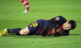 Lionel Messi, do Barcelona, reage após ser lesionado em partida contra o Benfica no estádio de Nou Camp em Barcelona. 5/12/2012 REUTERS/Sérgio Charmona