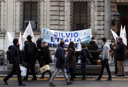Residents walk past a banner reading ''Silvio, Italy believes in you'' hung outside former Prime Minister Silvio Berlusconi's home in central Rome December 6, 2012. REUTERS/Alessandro Bianchi