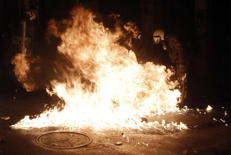 A riot policeman tries to avoid flames from a molotov cocktail thrown by a protester after a rally marking the 2008 shooting of a student by police in Athens December 6, 2012. REUTERS/John Kolesidis