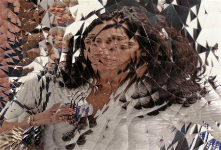 An art patron is reflected in an Untitled piece by Anish Kapoor at Art Basel in Miami Beach, Florida December 5, 2012. REUTERS/Robert Sullivan