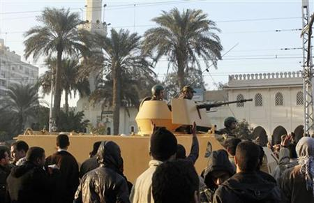 Supporters of the Muslim Brotherhood welcome tanks arriving outside the Egyptian presidential palace in Cairo December 6, 2012. REUTERS/Asmaa Waguih