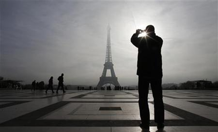 A tourist takes a picture of the Eiffel tower as he visits the Trocadero square in Paris November 9, 2012. REUTERS/Christian Hartmann