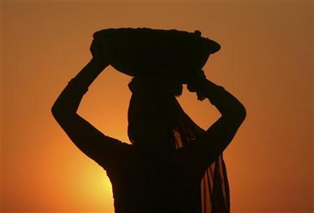 A woman labourer carrying cement is silhouetted against the setting sun at the site of a commercial complex on the outskirts of Jammu November 22, 2012. REUTERS/Mukesh Gupta