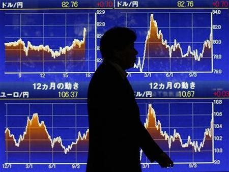 A man walks past an electronic board showing the graphs of exchange rates between the Japanese Yen and the U.S. dollar outside a brokerage in Tokyo November 22, 2012. REUTERS/Kim Kyung-Hoon
