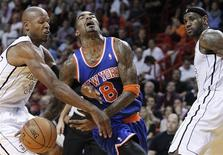 Miami Heat's Ray Allen (L) fouls New York Knicks' J.R. Smith (C) as the Heat's LeBron James (R) looks on in the send half of their NBA basketball game in Miami, Florida December 6, 2012. REUTERS/Andrew Innerarity