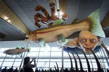 A woman takes a photo of a giant sculpture of J. R. R. Tolkien character Gollum at Wellington International Airport November 27, 2012. REUTERS/Mark Coote