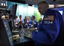 Трейдеры работают в торговом зале биржи в Нью-ЙоркеЮ 5 декабря 2012 года. Американские акции завершили торги четверга небольшим ростом благодаря сектору высоких технологий во главе с Apple. REUTERS/Brendan McDermid