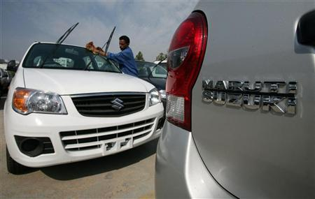 A worker cleans a parked car at the Maruti Suzuki's stockyard on the outskirts of Jammu October 30, 2010. REUTERS/Mukesh Gupta/Files