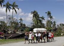 Los residentes en el sur de Filipinas comenzaron a enterrar a sus muertos el viernes aún cuando los equipos de rescate siguen recorriendo zonas remotas en busca de posibles supervivientes del tifón Bopha, la tormenta más fuerte que ha golpeado este año al país, que causó 418 muertos y casi la misma cantidad de desaparecidos. En la imagen del 6 de diciembre, unos filipinos llevan un ataúd con una víctima del tifón pasando por delante de una casa destruida en el pueblo de Nuevo Batán, en la provincia de Valle de Compostela, en el sur del archipiélago. REUTERS/Erik De Castro