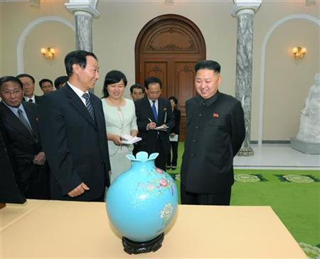 North Korean leader Kim Jong-Un (R) and Wang Jiarui (front L), the head of the International Liaison Department of China's Communist Party, talk in front of a present during their meeting in Pyongyang August 2, 2012 in this picture released by the North's official KCNA news agency on August 3, 2012. REUTERS/KCNA/Files