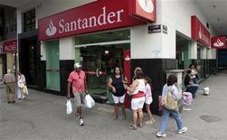Banco Santander Brasil dijo el jueves que despedirá a unos 1.000 empleados esta semana como parte de sus medidas para reducir costes en medio de una expansión lenta de la economía brasileña, menores márgenes y tipos bajas. Imagen de unos brasileños pasando ante una sucursal de Santander en el barrio de Copacabana de Río de Janeiro el pasado mes de mayo. REUTERS/Sergio Moraes