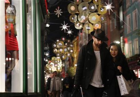 A couple walk past a shop window in London November 13, 2012. REUTERS/Luke MacGregor