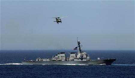 A U.S. Navy helicopter flies over a U.S. warship as they participate in joint military exercises between the U.S. and South Korea in South Korea's East Sea July 26, 2010. REUTERS/Lee Jin-man/Pool