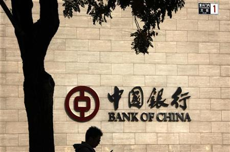 A man checks his mobile phone as he walks past the head office of Bank of China in Beijing October 25, 2012. REUTERS/David Gray