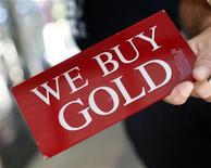 """Человек держит табличку с надписью """"Мы покупаем золото"""" в Нью-Йорке, 19 июля 2011 года. Цены на золото почти неподвижны после роста в четверг, вызванного перспективой снижения процентных ставок Европейского центрального банка, и могут снизиться вторую неделю подряд REUTERS/Shannon Stapleton"""