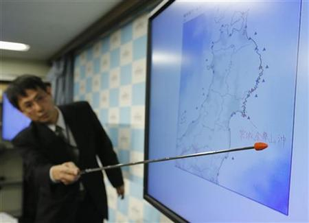 Japan Meteorological Agency's Senior Coordinator for Seismological Information Makoto Saito points to the spot showing the centre of a magnitude 7.3 earthquake, during a news conference in Tokyo December 7, 2012. REUTERS/Toru Hanai