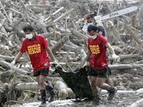 Pessoas do resgate carregam corpos de vítimas do tufão Bopha em sacos, após retirá-los dos escombros, na cidade de New Bataan, em Compostela Valley, no sul das Filipinas. Moradores do sul das Filipinas enterraram nesta sexta-feira os mortos, enquanto equipes de resgate continuavam vasculhando áreas remotas em busca de sobreviventes do tufão Bopha, que matou 418 pessoas e deixou quase o mesmo número de desaparecidos. 7/12/2012 REUTERS/Erik De Castro