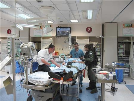 An Israeli soldier stands next to doctors as they treat a wounded Austrian peacekeeping soldier at Rambam Hospital in the northern Israeli city of Haifa, in this handout photo obtained by Reuters from a Rambam Hospital spokesperson on November 30, 2012. REUTERS/Rambam Hospital/Handout