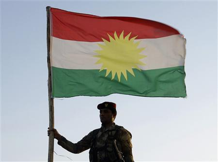 A Kurdish Peshmerga soldier holds a Kurdistan flag during a deployment in the area near the northern Iraqi border with Syria, which lies in an area disputed by Baghdad and the Kurdish region of Ninawa province, in this August 6, 2012 file photo. For all the flag-waving and warnings of war from Iraqi Prime Minister Nuri al-Maliki and Kurdistan President Masoud Barzani, few believe either will risk an all-out conflict whose outcome would be uncertain and would disrupt both a flourishing economy in Kurdistan and oil exports that bring Baghdad vital revenues. REUTERS/Azad Lashkari/Files