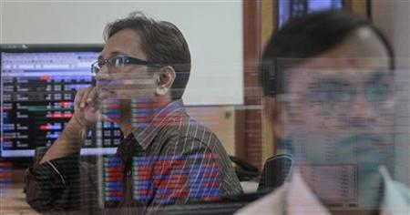 A broker (L) watches a TV news channel as another monitors share prices at a brokerage firm in Mumbai August 9, 2011. REUTERS/Danish Siddiqui/Files