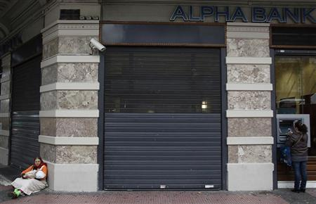 A woman makes a transaction at the automated teller machine (ATM) as another begs outside an Alpha bank branch in central Athens November 29, 2012. REUTERS/John Kolesidis