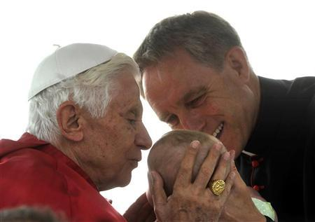 Pope Benedict XVI kisses a child held by private secretary Monsignor Georg Ganswein (R) before conducting mass at Bresso airport near Milan June 3, 2012. REUTERS/Paolo Bona