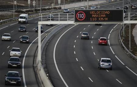 Vehicles drive past an electronic board reminding drivers of the new speed limit on a highway outside Madrid March 7, 2011. REUTERS/Susana Vera