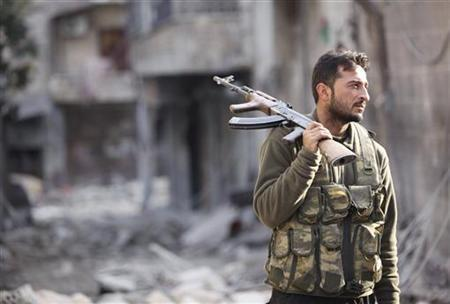 A Free Syrian Army fighter holds his rifle as he stands on a damaged street in Aleppo's Karm al-Jabal district November 29, 2012. Picture taken November 29, 2012. REUTERS/Zain Karam
