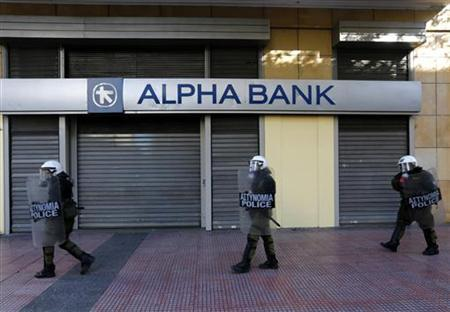 Riot policemen walk by a closed branch of Alpha Bank during a rally to mark the 2008 shooting of a student by police in Athens' Syntagma (Constitution) square December 6, 2012. REUTERS/Yannis Behrakis