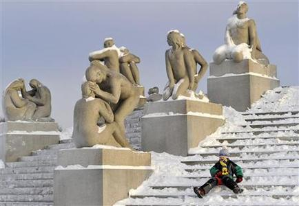 A child toboggans down snow covered steps past sculptures in the Vigeland Sculpture Park in Oslo December 11, 2010. REUTERS/Toby Melville