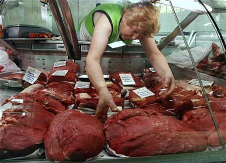 A butcher arranges portions of meat in her display at a market in St. Petersburg June 2, 2011. REUTERS/Alexander Demianchuk