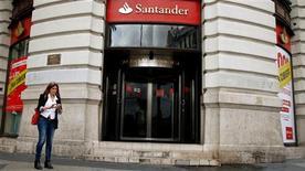 La bolsa española cerró el viernes con caídas una jornada de pocas referencias, entre las que destacó las peores previsiones de crecimiento en Alemania, con lastre del preponderante sector bancario. En esta imagen de archivo, una mujer utiliza su teléfono móvil frente a una sucursal de Banco Santander en Madrid, el 25 de octubre de 2012. REUTERS/Sergio Pérez
