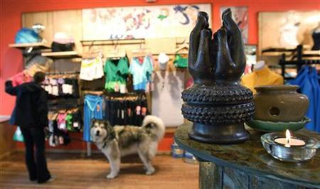 A Buddha shrine sits at the entrance of Lululemon Athletic, a yoga clothing store, as a woman shops with her dog in San Francisco, California, in this March 31, 2006 file photo. REUTERS/Kimberly White/Files
