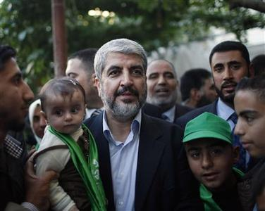 Hamas leader Khaled Meshaal holds the grandchild of late Hamas founder Sheikh Ahmed Yassin in Gaza City December 7, 2012. REUTERS/Ahmed Jadallah