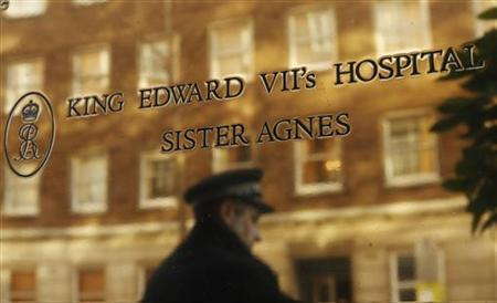 A police officer is reflected as he stands outside King Edward VII hospital, a day after Catherine, Duchess of Cambridge was discharged in central London December 7, 2012. REUTERS/Olivia Harris