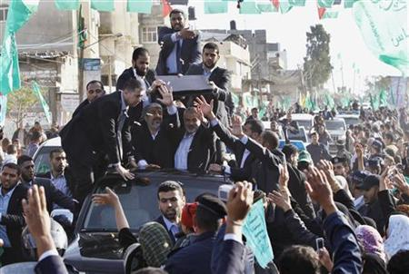 Hamas chief Khaled Meshaal (front L) waves to the crowd as he rides in a car beside senior Hamas leader Ismail Haniyeh (front R) in Gaza December 7, 2012. REUTERS/Ahmed Jadallah