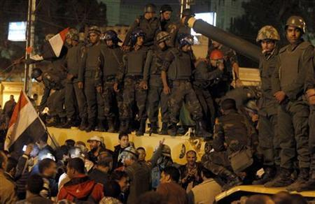 Republican Guard soldiers stand on a tank as they are surrounded by protesters against Egypt's President Mohamed Mursi after the protesters peacefully broke past barbed wire barricades guarding the presidential palace in Cairo December 7, 2012. REUTERS/Mohamed Abd El Ghany