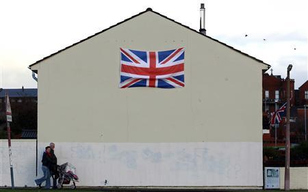 People walk past a house displaying a Union flag in the Shankill Road area of West Belfast December 7, 2012. U.S. Secretary of State Hillary Clinton travelled to Northern Ireland on Friday to lend her support to the British province's fragile peace, the frailty of which was underlined by overnight rioting on the eve of her visit and the seizure of a bomb. REUTERS/Cathal McNaughton