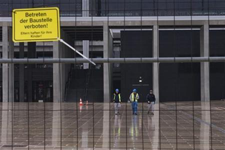 Workers walk outside the main terminal of the Berlin-Brandenburg international airport (BER) outside Berlin, November 1, 2012. REUTERS/Thomas Peter