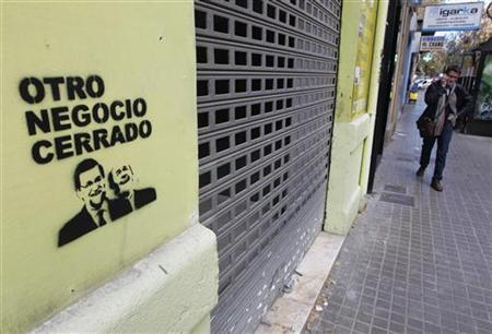 A graffiti with the image of Spanish Prime Minister Mariano Rajoy and opposition leader Alfredo Perez Rubalcaba is seen on the facade of a closed shop in Valencia, December 7, 2012. REUTERS/Heino Kalis