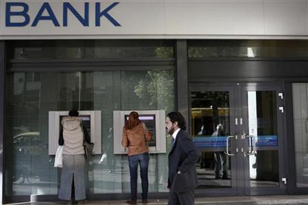 People make transactions at ATMs of an Alpha bank branch in Athens December 7, 2012. REUTERS/Yorgos Karahalis