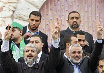 Hamas chief Khaled Meshaal (L) and senior Hamas leader Ismail Haniyeh flash victory signs upon arrival at a rally marking the 25th anniversary of the founding of Hamas, in Gaza City December 8, 2012. After receiving a hero's welcome on his return from decades in exile, Hamas leader Khaled Meshaal will attend a rally in Gaza on Saturday to mark the founding of his Islamist group and celebrate ''victory'' over Israel. REUTERS/Mohammed Salem
