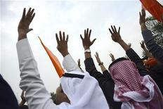 Pessoas, erguendo quatro dedos em uma mão, observam um helicóptero da polícia em manifestação contra novas regras eleitorais na Cidade do Kuweit, Kuweit. 8/12/2012 REUTERS/Stephanie McGehee
